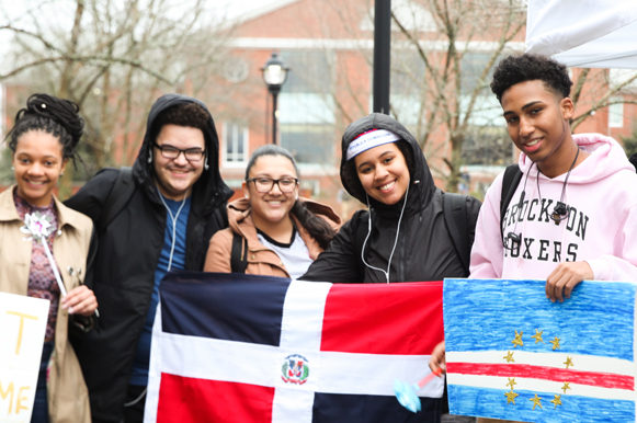 five students hold international flags on bentley's campus