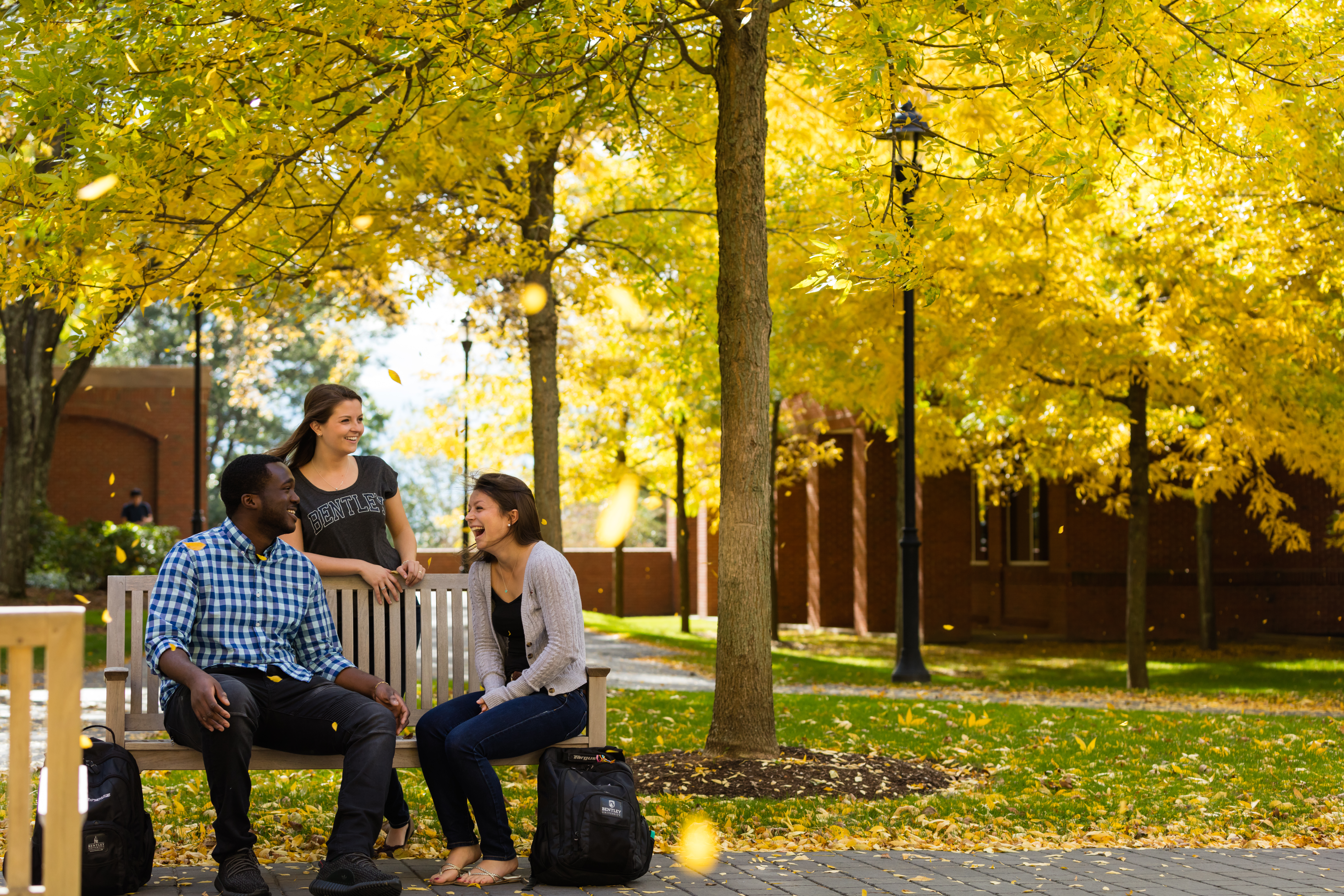 three students talk on bentley's campus