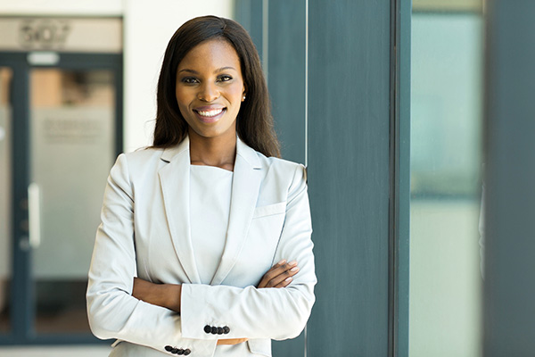 Black woman in a white suit folding her arms and smiling