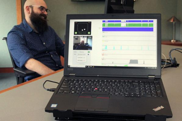 Laptop running eye tracking software with a participant in the background.