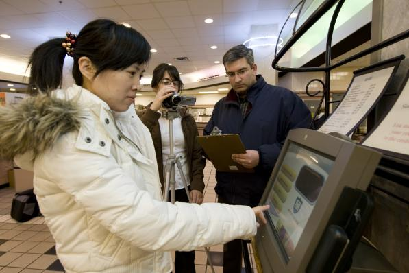 Two researchers observing a woman operating a touch screen kiosk in a shopping center.