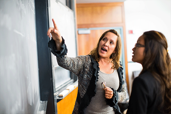 Professor at chalkboard explaining to student