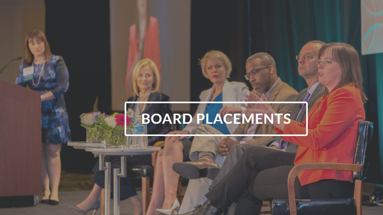Image of 5 speakers, two men and three women, sitting on stage with a woman panelist