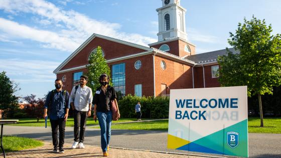 Students walking on campus near a sign saying Welcome Back