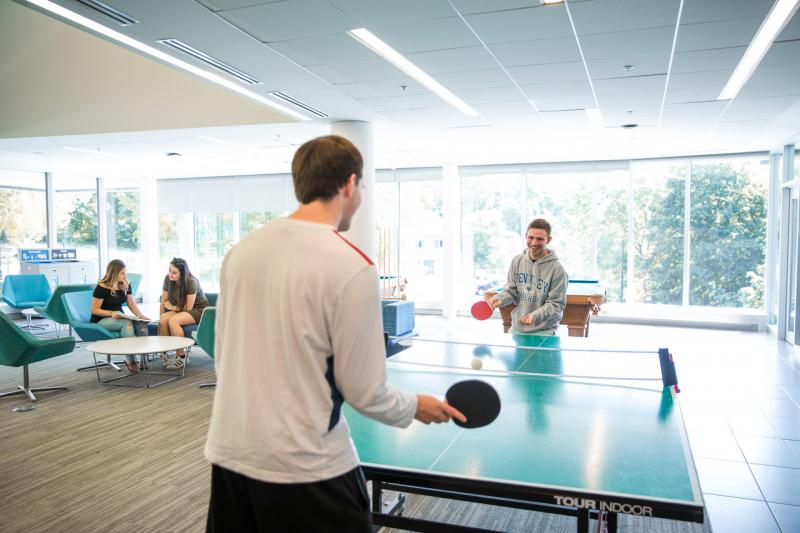 two male students playing ping pong