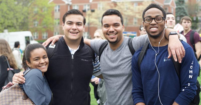 students smile together at an event on campus