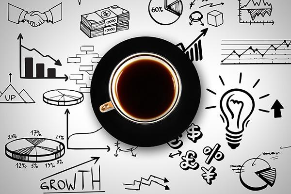 Cup of coffee surrounded by drawings of business related charts and icons